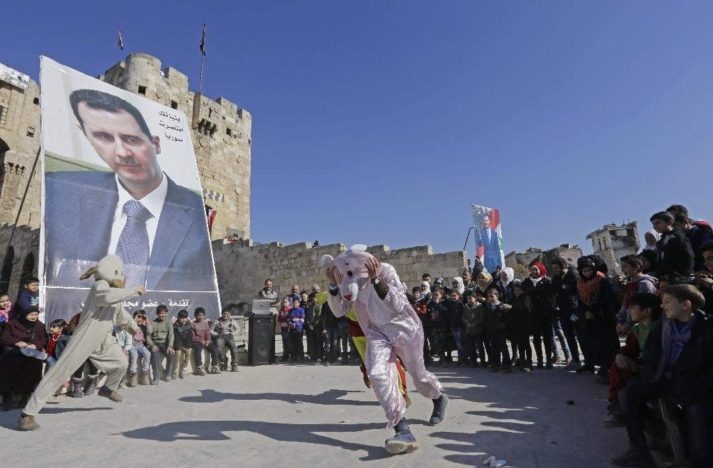 Syrians perform in front of a large poster of President Bashar al-Assad outside the Aleppo Citadel on January 22, 2017 (AFP Photo/LOUAI BESHARA)