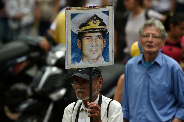 A man holds a sign with the portrait of late Venezuelan retired naval officer Rafael Acosta during a march against the government in Caracas in July 2019
