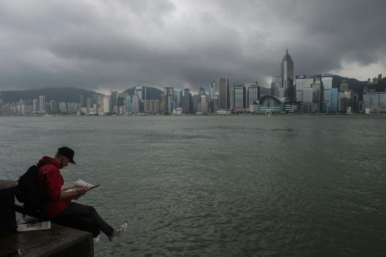 A man reads a newspaper on the edge of a promenade overlooking Victoria Harbour in Hong Kong (AFP Photo/Anthony WALLACE)