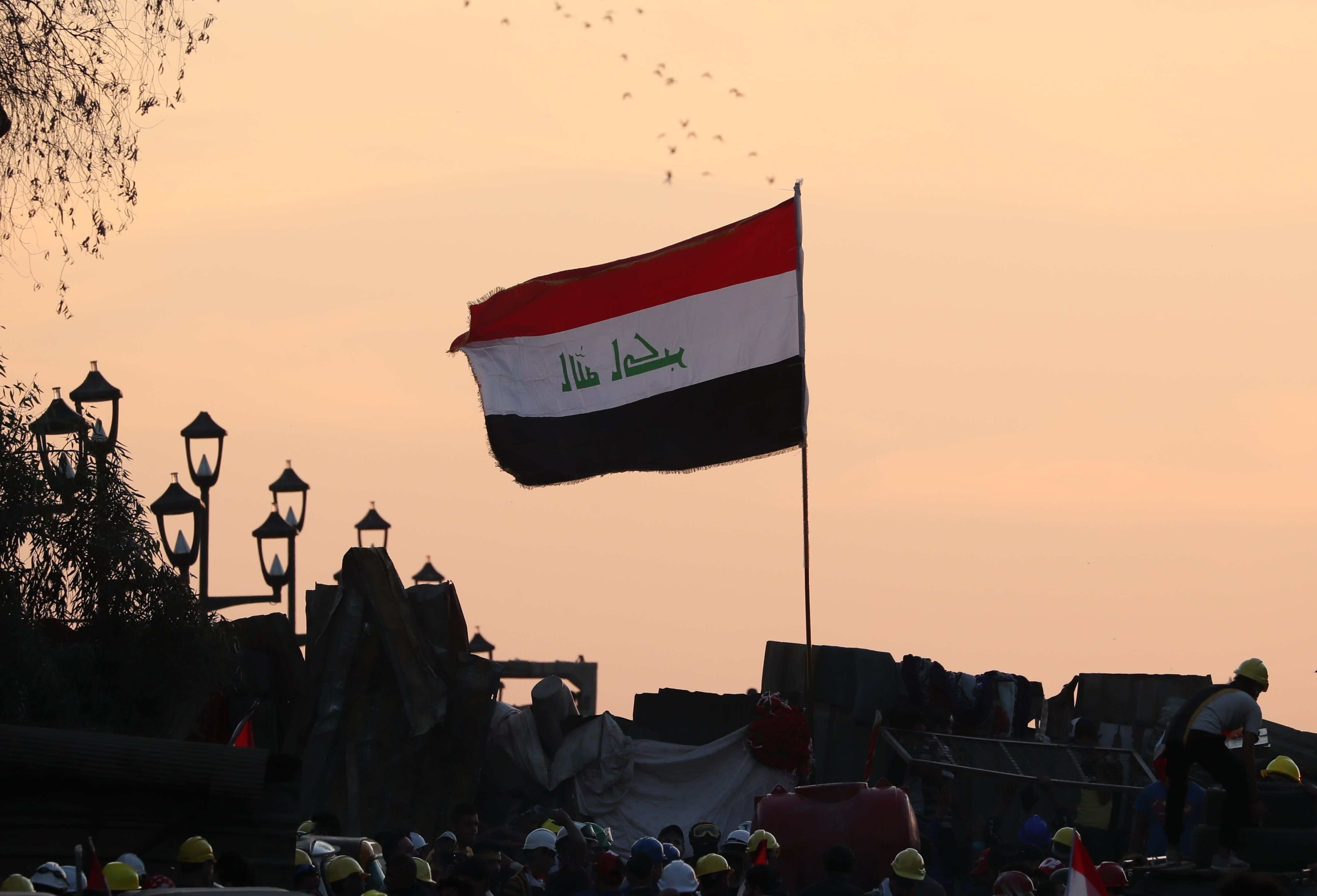 Anti-government protesters stand on barriers set up by Iraqi security forces in an effort to close a bridge leading to the Green Zone government area, during ongoing protests in Baghdad, Iraq, Tuesday, Nov. 5, 2019. (AP Photo/Hadi Mizban)