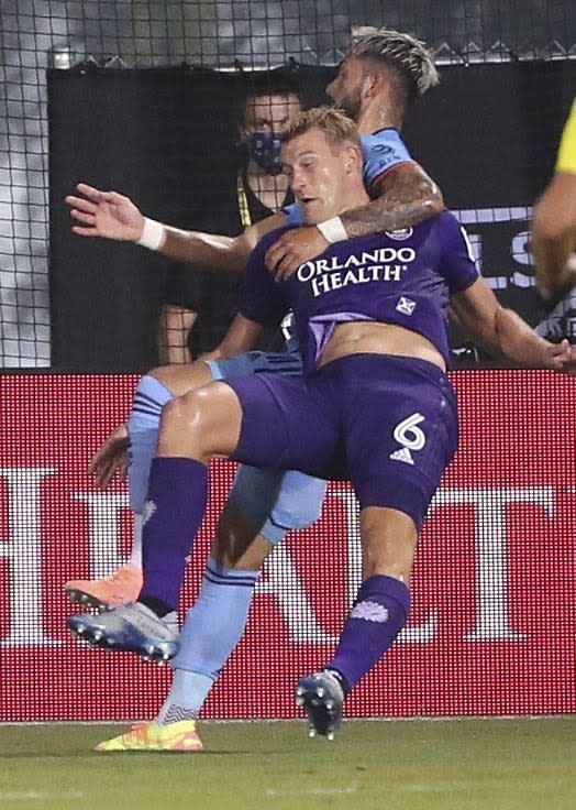 New York City FC's Valentin Castellanos, rear, pulls down Orlando City's Robin Jansson (6) during the MLS is Back tournament soccer match, Tuesday, July 14, 2020, in Lake Buena Vista, Fla. Castellanos received a yellow card for the rough play. (Stephen M. Dowell/Orlando Sentinel via AP)