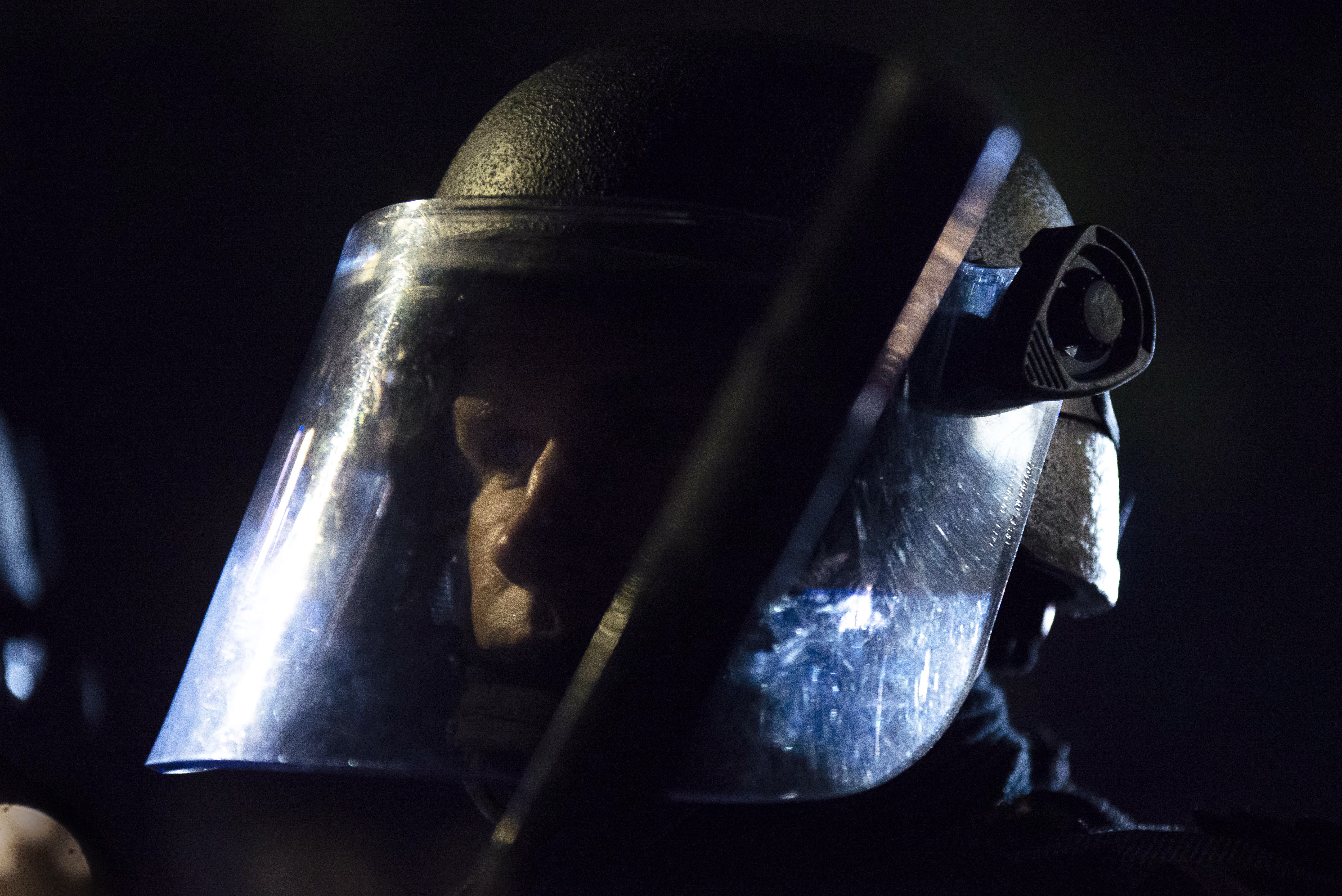 A Portland police officer watches a crowd of protesters at the Laurelhurst neighborhood early in the morning on Saturday, Aug. 8, 2020 in Portland, Ore. (AP Photo/Nathan Howard)