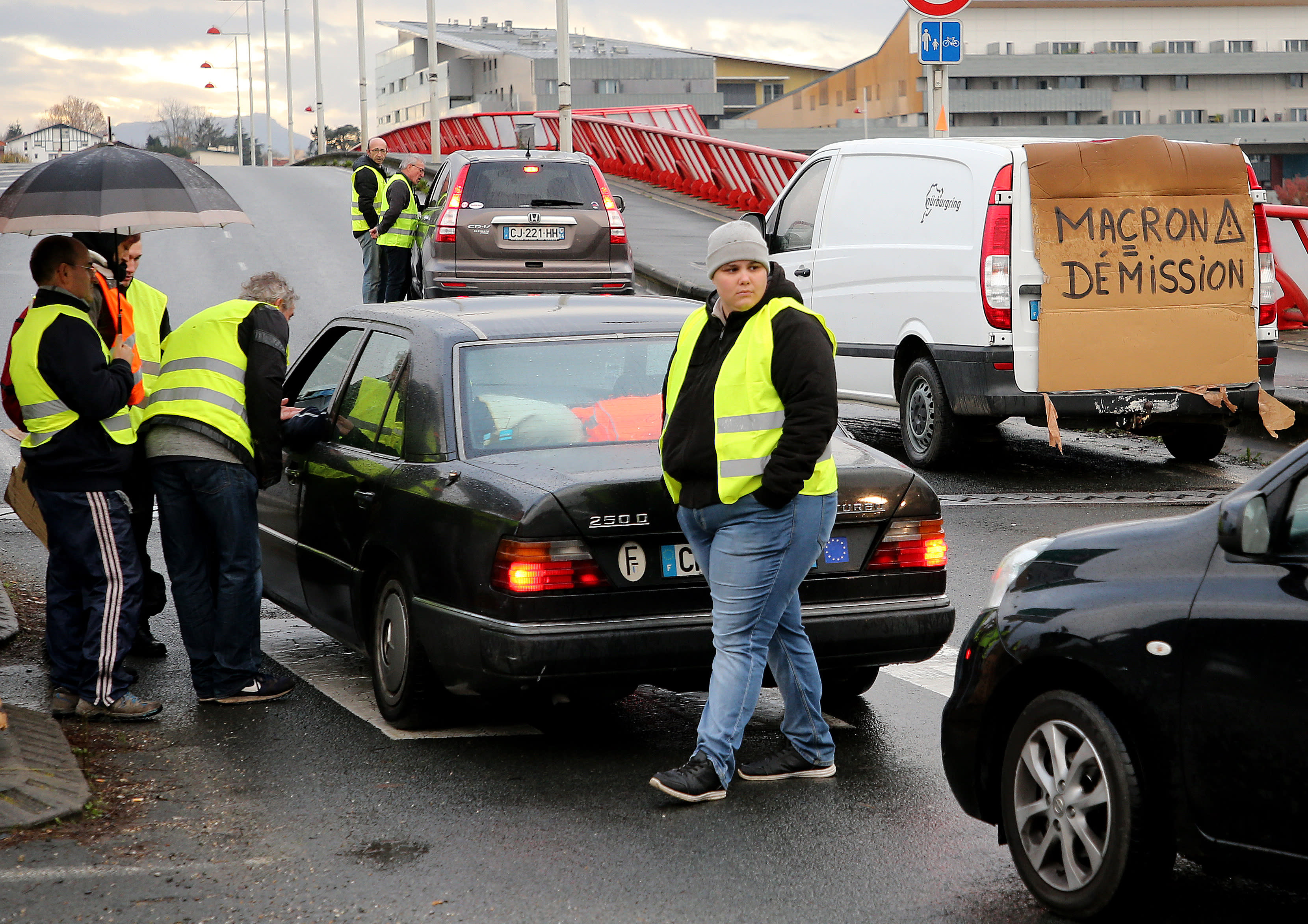 Demonstrators block cars in Bayonne, southwestern France, Sunday, Nov. 18, 2018. One protester was killed and 227 other people were injured — eight seriously — at roadblocks set up around villages, towns and cities across France on Saturday as citizens angry with rising fuel taxes rose up in a grassroots movement, posing a new challenge to beleaguered President Emmanuel Macron. (AP Photo/Bob Edme)