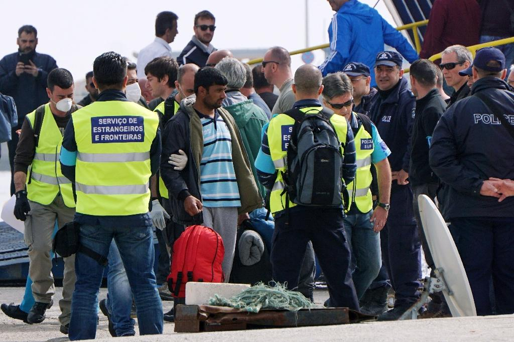 Frontex officials and Greek police stand with migrants which are to be deported back to Turkey on April 8, 2016 in the port of Mytilene on the Greek island of Lesbos (AFP Photo/STRINGER)