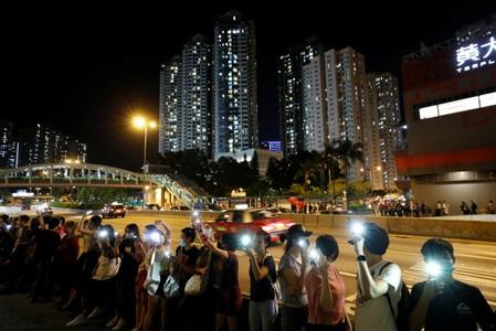 Protesters light up their smartphones as they form a human chain during a rally to call for political reforms in Hong Kong
