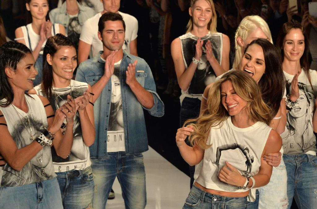 Brazilian supermodel Gisele Bundchen is applauded by fellow models wearing T-shirts with her image on them as Bundchen makes her last appearance before retiring at the 2016 Summer collections of the Sao Paulo Fashion Week, on April 15, 2015 (AFP Photo/Nelson Almeida)