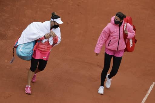 Victoria Azarenka of Belarus, right, and Montenegro's Danka Kovinic walk onto the court to resume the first round match of the French Open tennis tournament against at the Roland Garros stadium in Paris, France, Sunday, Sept. 27, 2020. (AP Photo/Alessandra Tarantino)
