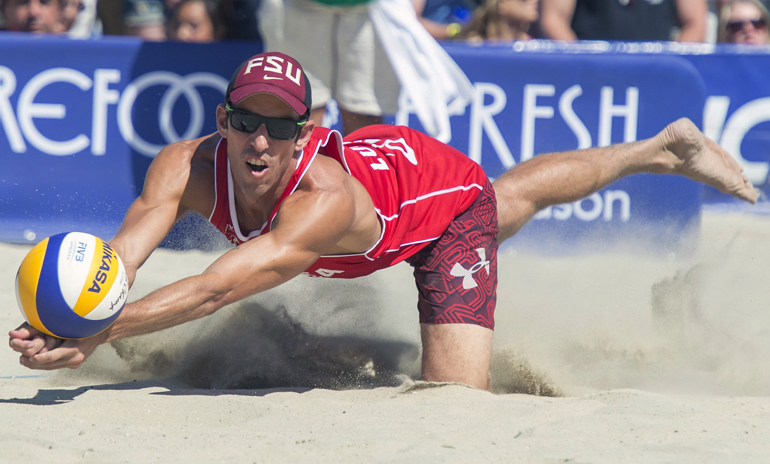 FILE - In this Aug. 23, 2015, filer photo, United States' Nick Lucena digs out a ball during the final match at the FIVB World Series of Beach Volleyball event in Long Beach, Calif. Organizers of the AVP beach volleyball tour gathered at their Orange County war room to try to salvage as much as possible of their season as the cancellations mounted in the sports world. Ideas tossed out included everything from a fan-free setup on a local beach to playing in front of a green screen in a TV studio. But with the suspension of the NBA season, it became obvious that scrapping any events before June was the only choice. (Michael Goulding/The Orange County Register via AP, File)
