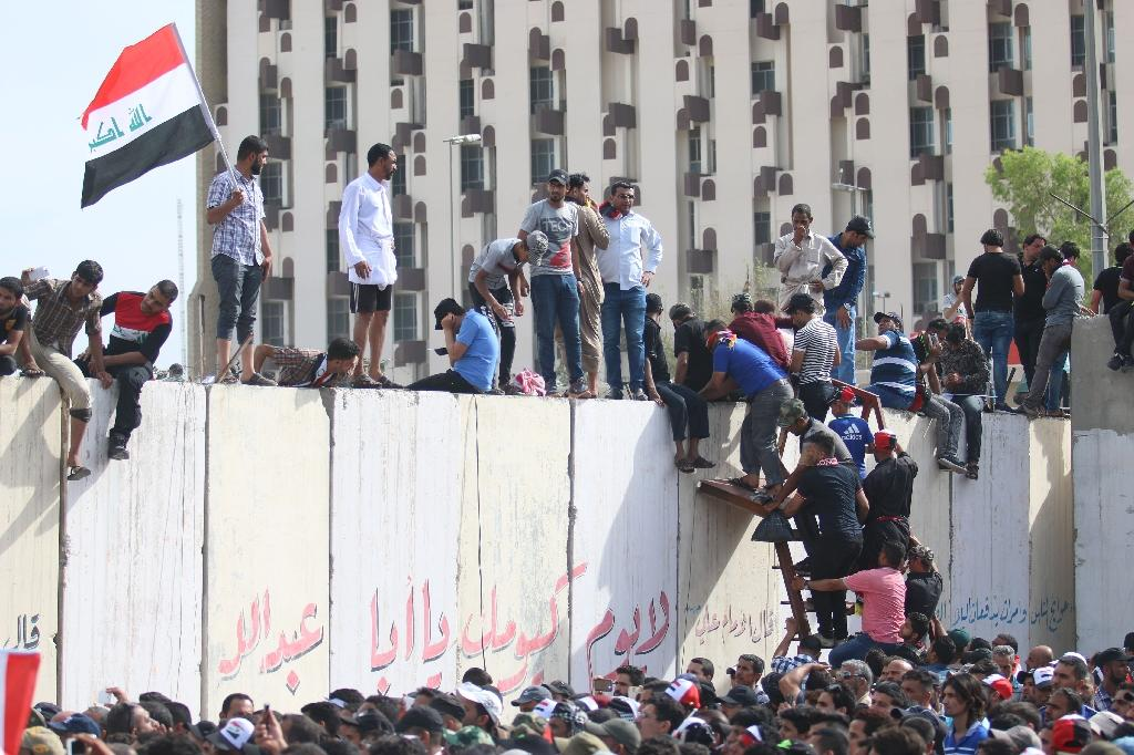 """Iraqi protesters climb over a concrete wall surrounding the parliament after breaking into Baghdad's heavily fortified """"Green Zone"""" on April 30, 2016 (AFP Photo/Haidar Mohammed Ali)"""