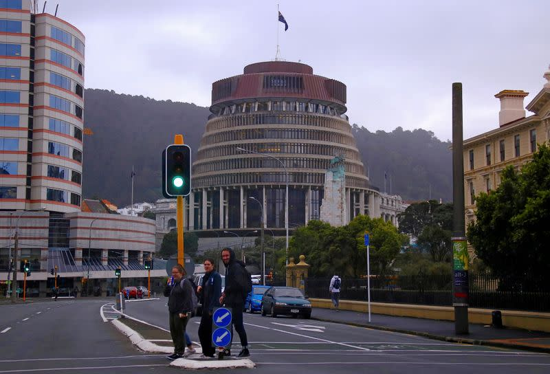 Pedestrians walk across a road in front of the New Zealand parliament building known as the Beehive in central Wellington, New Zealand