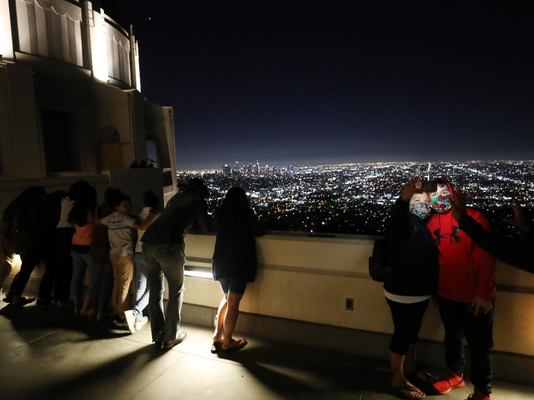 People pose for a photo while wearing face masks at Griffith Observatory with downtown in the background amid the COVID-19 pandemic on July 16, 2020 in Los Angeles, California.