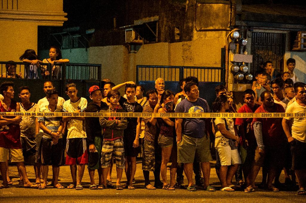 Residents behind a police line look at two dead bodies after a drug bust operation that turned into a gun fight in the Philippine capital Manila on July 19, 2016 (AFP Photo/Noel Celis)