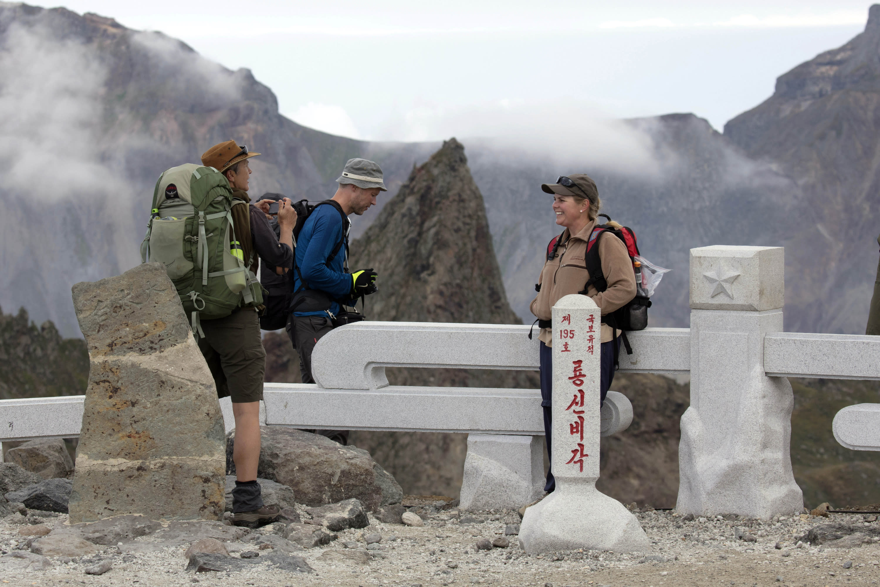 In this Saturday, Aug. 18, 2018, photo, Sinead of Australia, right, chats with Paula of Australia, left, and Tarjei Naess Skrede of Norway during a hike arranged by Roger Shepherd of Hike Korea on Mount Paektu in North Korea. Hoping to open up a side of North Korea rarely seen by outsiders, Shepherd, a New Zealander who has extensive experience climbing the mountains of North and South Korea is leading the first group of foreign tourists allowed to trek off road and camp out under the stars on Mount Paektu, a huge volcano that straddles the border that separates China and North Korea. (AP Photo/Ng Han Guan)