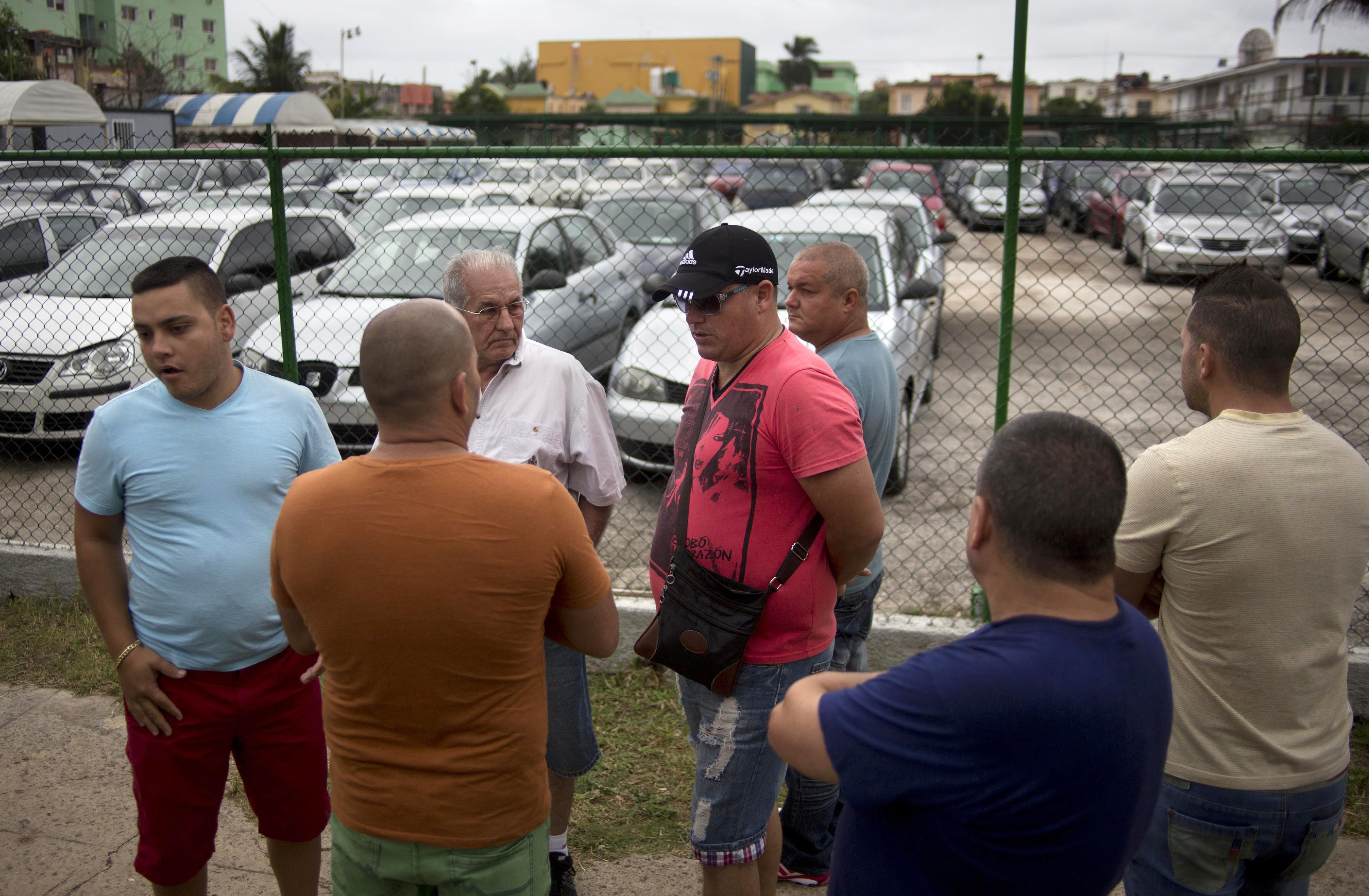 People gather outside a government-run car dealership that sells used vehicles in Havana, Cuba, Friday, Jan. 3, 2014. Cubans are eagerly visiting car dealerships as a new law takes effect on Friday eliminating a special permit requirement that has greatly restricted vehicle ownership in the country. To their dismay they found sharply hiked prices on the first day the law was in force. In Cuba, the government retains its monopoly on a vehicle's market value. (AP Photo/Ramon Espinosa)