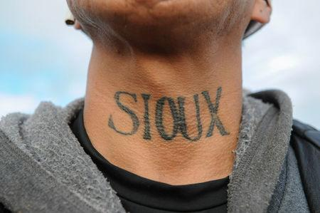 A man from the Lakota Sioux tribe with a Native American tattoo on his neck poses for a photograph during a protest against plans to pass the Dakota Access pipeline near the Standing Rock Indian Reservation, near Cannon Ball, North Dakota, U.S. November 16, 2016. REUTERS/Stephanie Keith