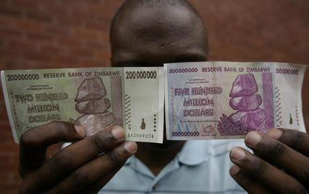 A man holds up newly issued 200 million and 500 million Zimbabwe dollar notes in the capital Harare