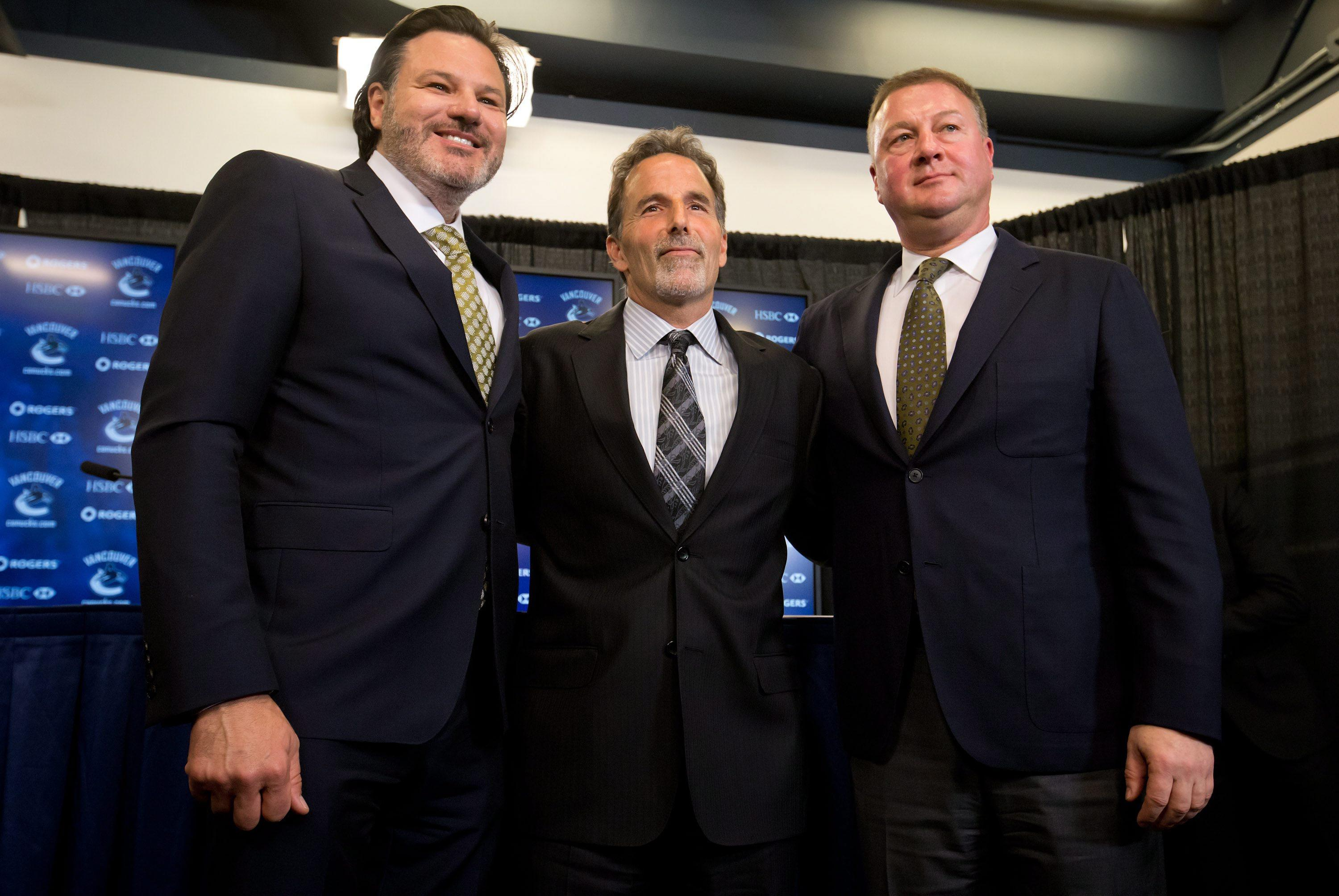 Vancouver Canucks new head coach John Tortorella, center, poses for photographs with owner Francesco Aquilini, left, and general manager Mike Gillis during an NHL hockey news conference announcing his hiring in Vancouver, British Columbia, on Tuesday June 25, 2013. (AP Photo/The Canadian Press, Darryl Dyck)