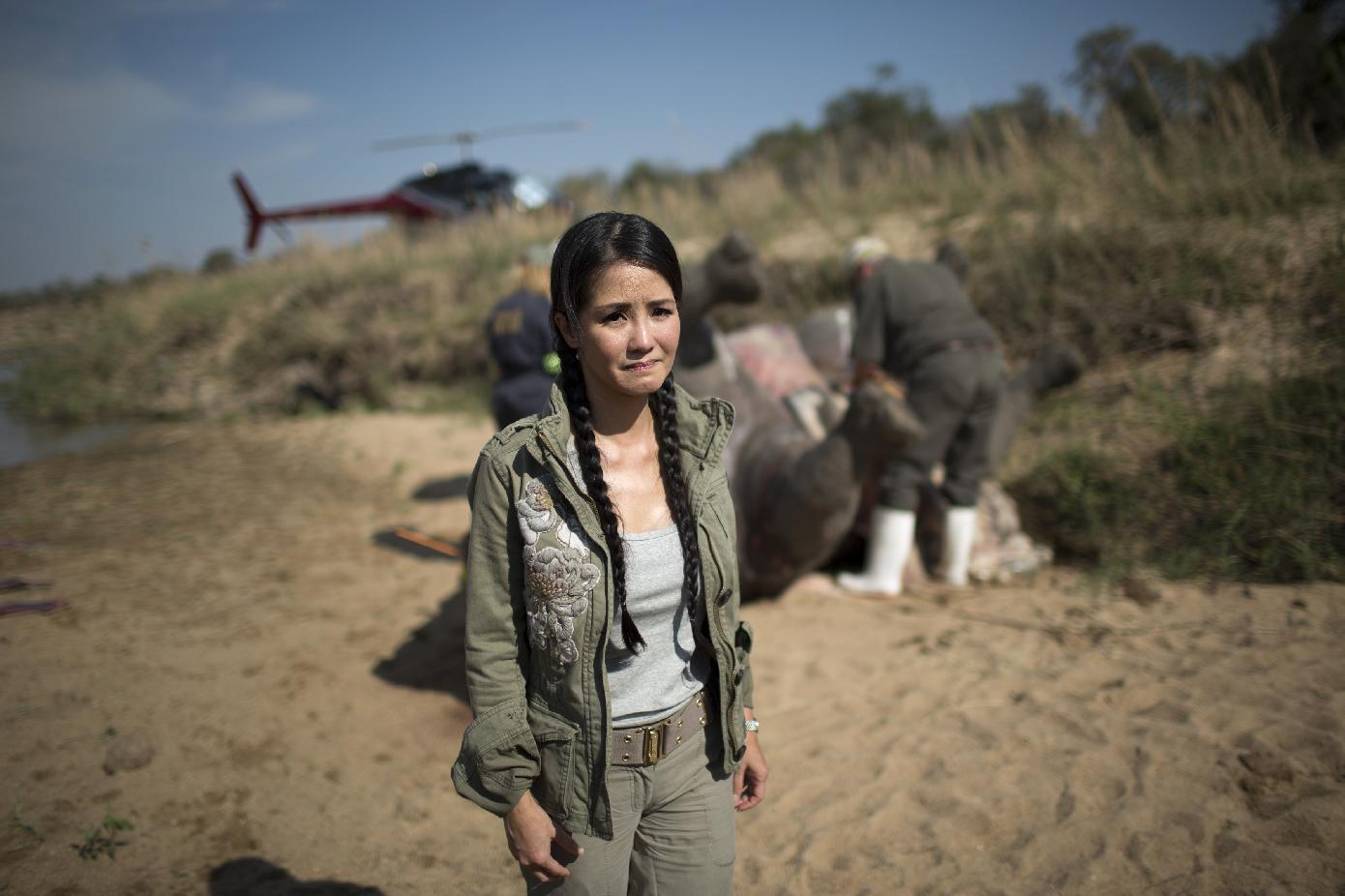 Vietnamese pop diva Hong Nhung, fights back tears as she stands near the carcass of a decomposing white rhino on the banks of a river in the Kruger National Park on September 12, 2014 (AFP Photo/Marco Longari)
