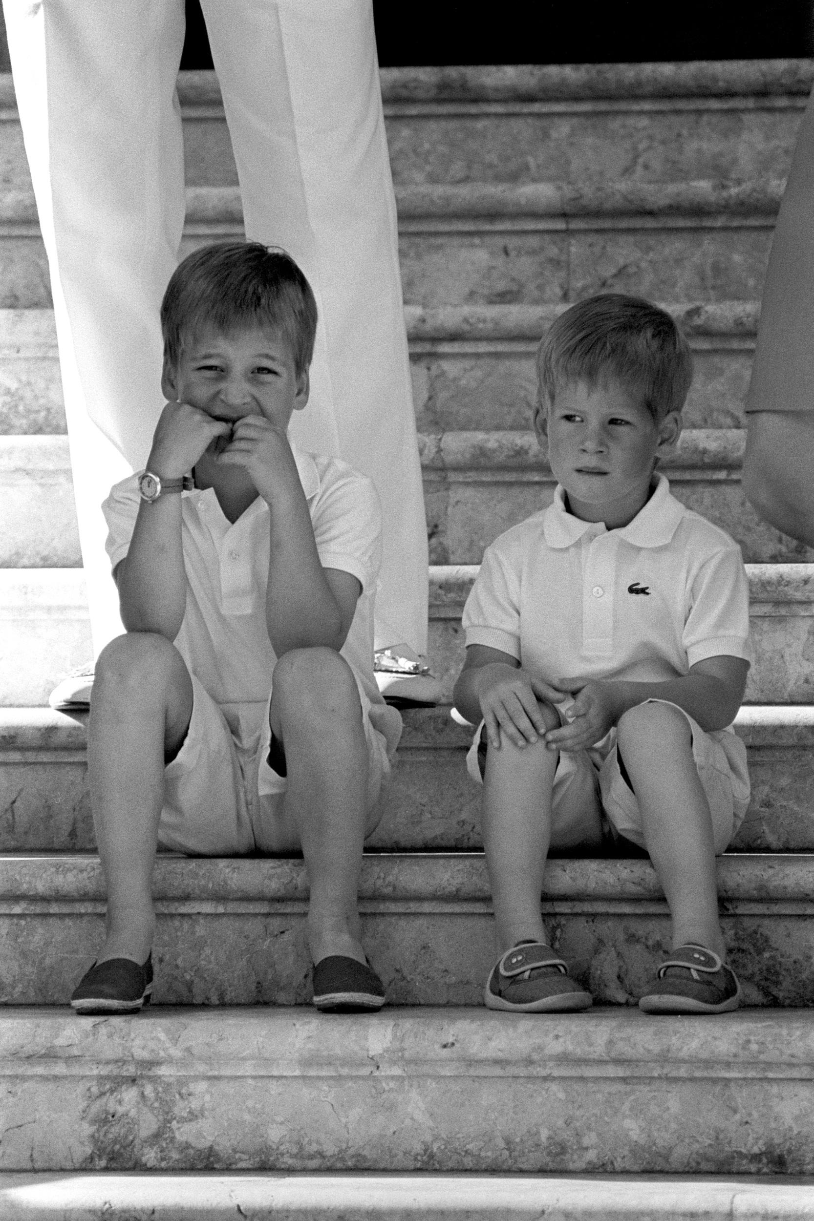 SIX YEAR OLD PRINCE WILLIAM (LEFT) AND HIS BROTHER PRINCE HARRY, 3, SITTING ON THE STEPS OF MARIVANT PALACE IN PALMA, MAJORCA. THE YOUNG PRINCES AND THEIR PARENTS, THE PRINCE AND PRINCESS OF WALES, WERE ON THEIR ANNUAL HOLIDAY WITH KING JUAN CARLOS OF SPAIN.   (Photo by Ron Bell - PA Images/PA Images via Getty Images)