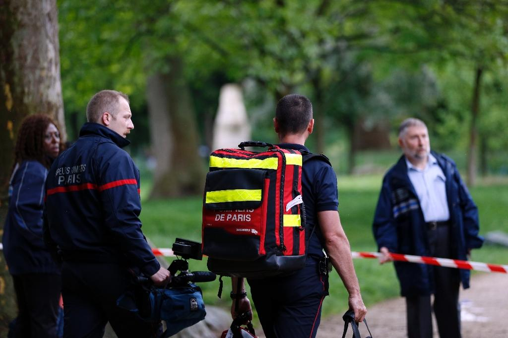 Firefigthers walk at the entrance of the Parc Monceau on May 28, 2016 in Paris, after eleven people including 10 children were struck by lightning in the parc