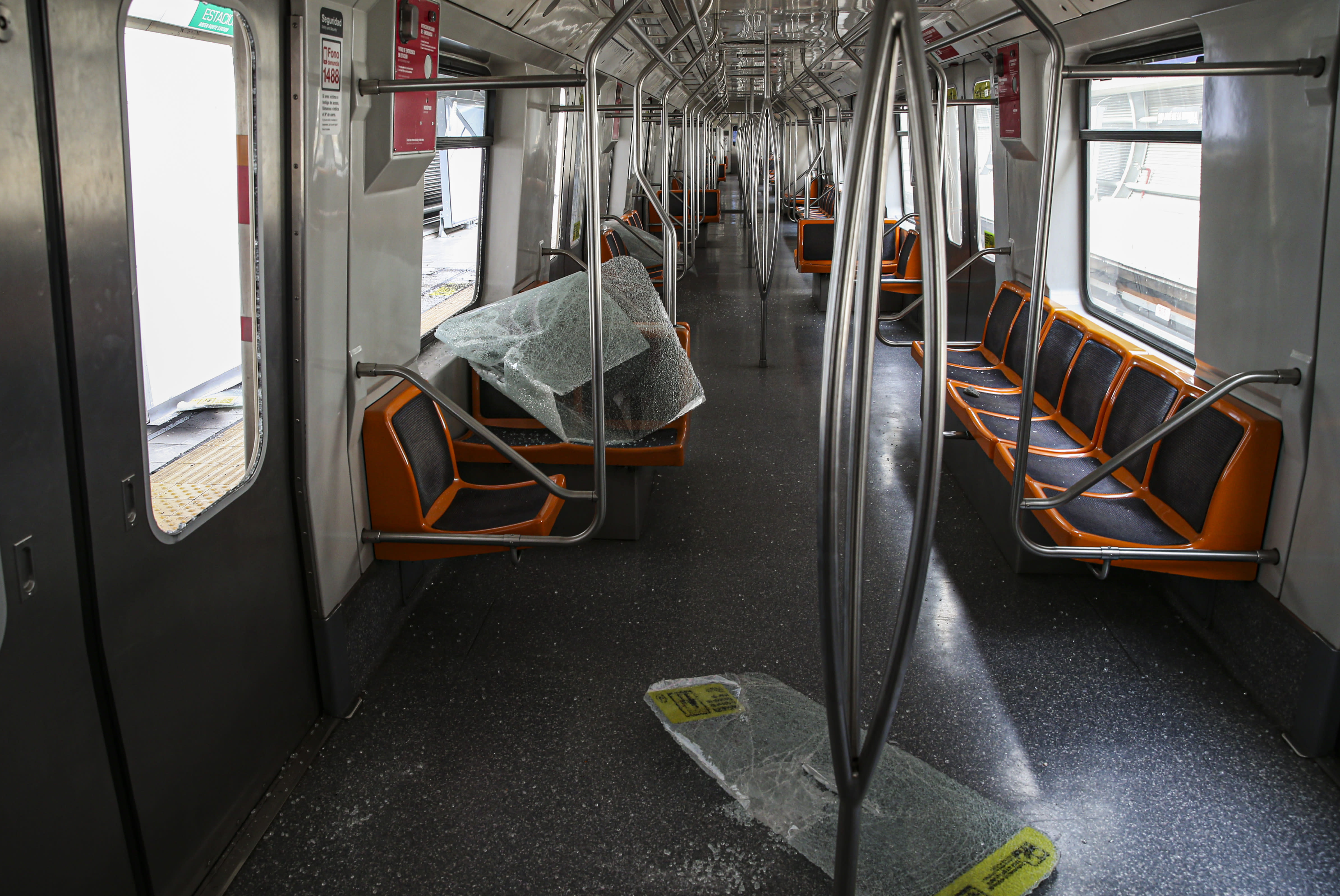 The destroyed windows of a subway car lay on the floor during a protest in Santiago, Chile, Saturday, Oct. 19, 2019. The protests started on Friday afternoon when high school students flooded subway stations, jumping turnstiles, dodging fares and vandalizing stations as part of protests against a fare hike, but by nightfall had extended throughout Santiago with students setting up barricades and fires at the entrances to subway stations. (AP Photo/Esteban Felix)
