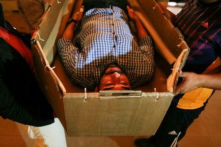 Elio Angulo lies inside a cardboard coffin as he introduces his product to potential customers at a mortuary in Valencia, in the state of Carabobo, Venezuela August 25, 2016. Picture taken August 25, 2016. REUTERS/Marco Bello