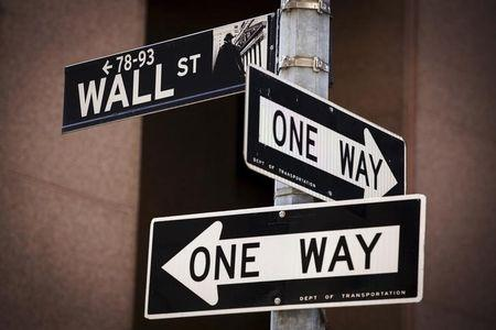 A 'Wall St' sign is seen above two 'One Way' signs in New York