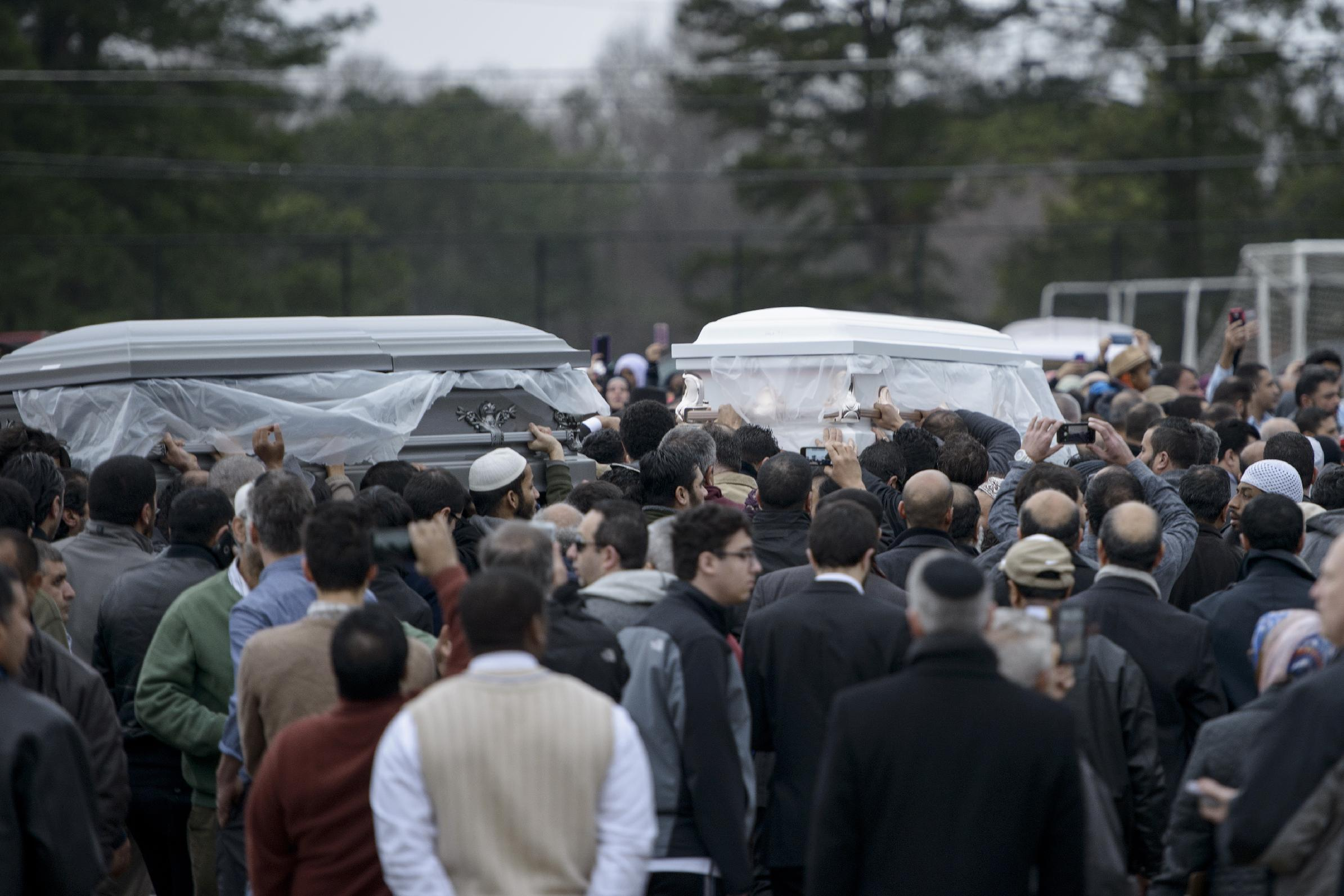 The remains of shooting victims are carried away after a service in a soccer field near the Islamic Association of Raleigh February 12, 2015, in Raleigh, North Carolina (AFP Photo/Brendan Smialowski)