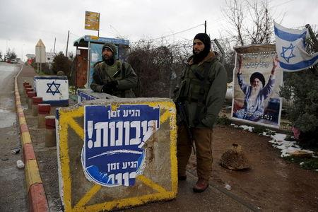 Israeli soldiers stand next to a concrete barrier as they guard near a bus stop in the Gush Eztion Jewish settlement bloc in the West Bank January 27, 2016. REUTERS/Amir Cohen