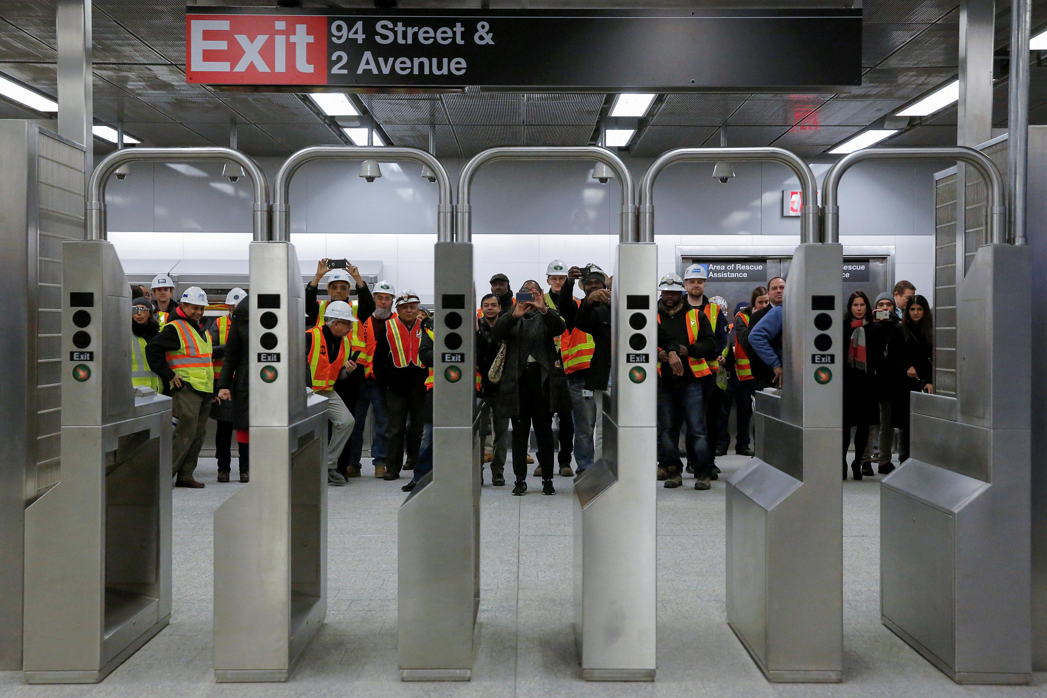 Workers take photos through the turnstyles at the 96th Street Station during a preview event for the Second Avenue subway line in Manhattan, New York City, U.S., December 22, 2016. REUTERS/Andrew Kelly