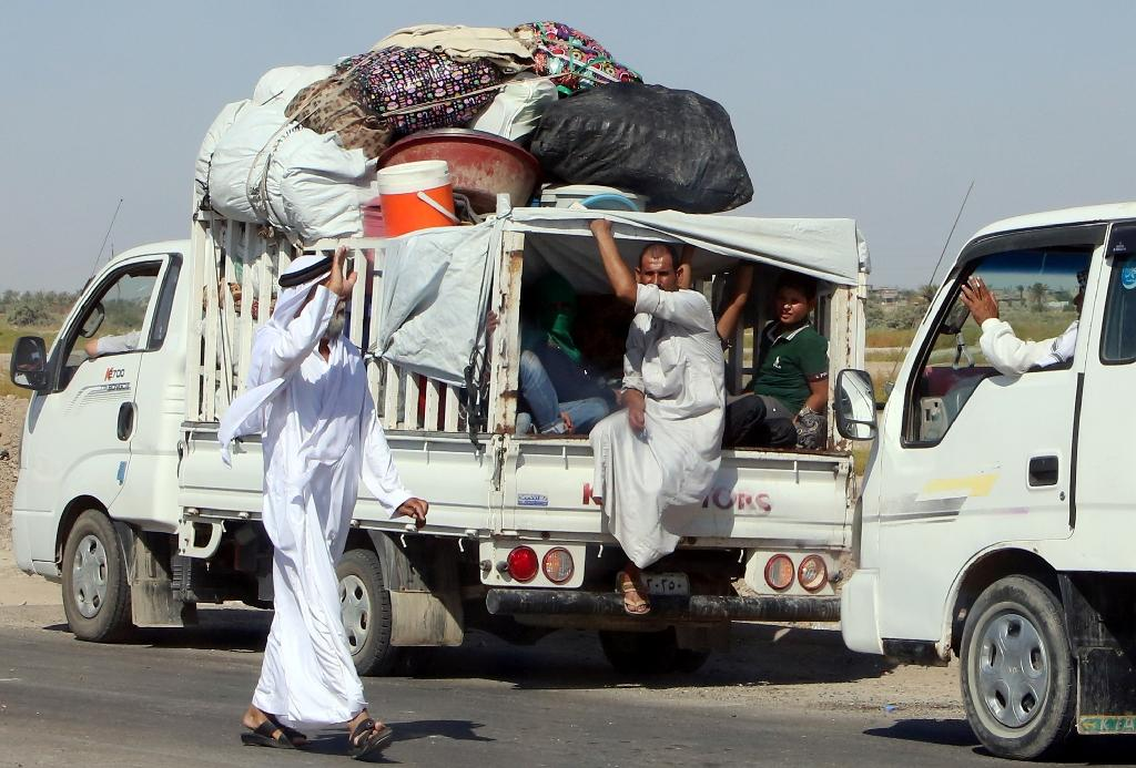 Iraqi families carry their belongings on the back of pick up trucks as they return to their homes in the city of Fallujah after Iraqi security forces retook the city back from the Islamic State (IS) jihadists (AFP Photo/Sabah Arar)