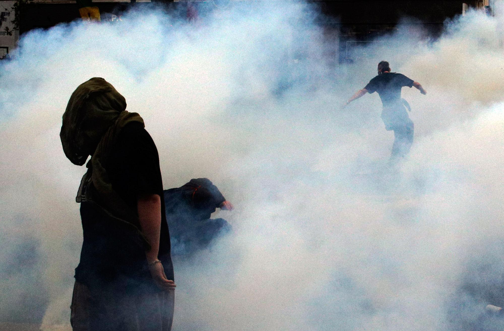 <p>Demonstrators are engulfed in tear gas smoke during scuffles with riot police following a protest against a labor law, in Paris, France, Thursday, Sept. 15, 2016. With strikes and protests, French unions are staging a last-ditch bid to dismantle a labor law that weakens their powers and worker protections. (AP Photo/Christophe Ena) </p>