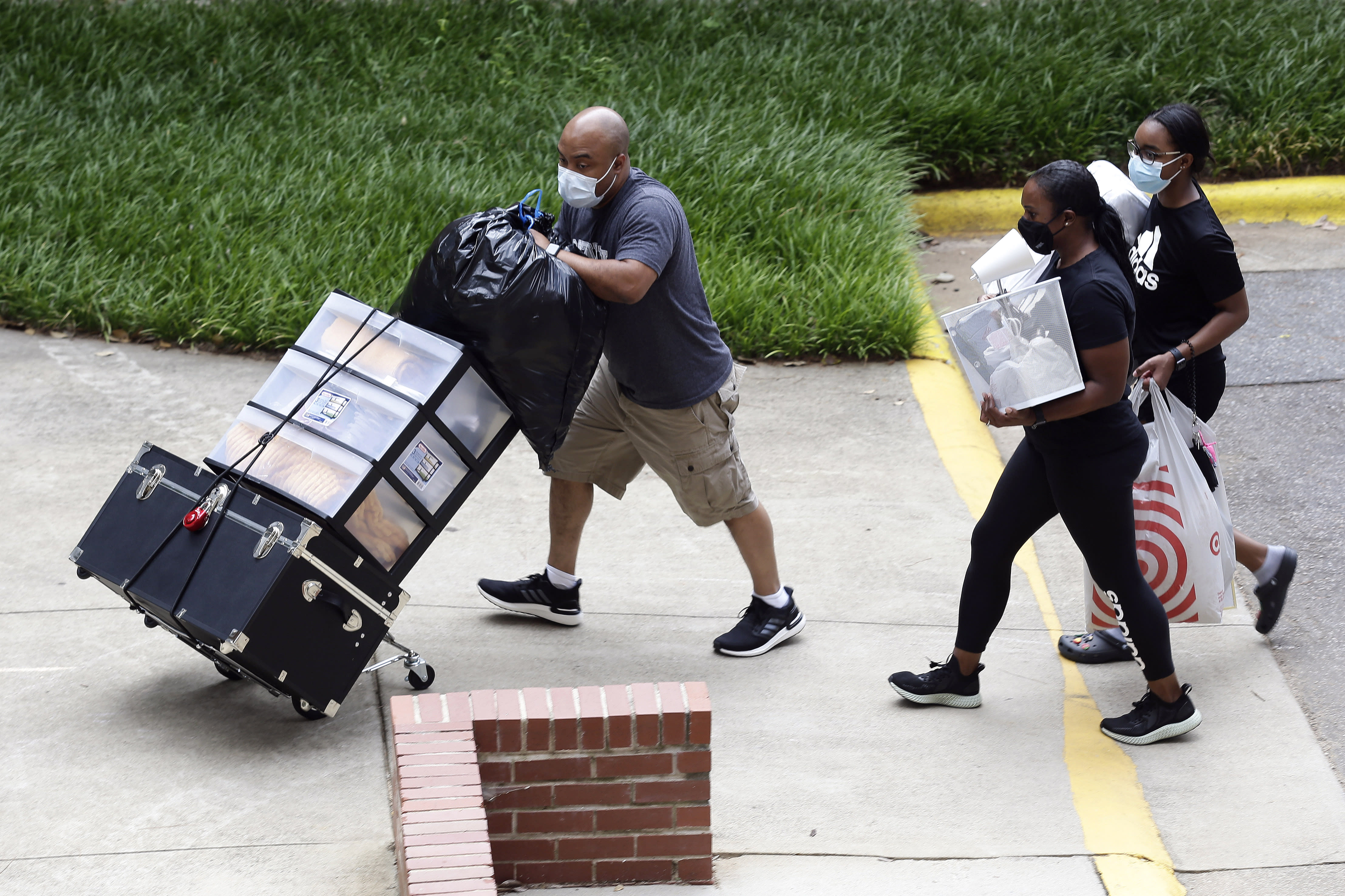 College students with the assistance of family begin moving in for the fall semester at N.C. State University in Raleigh, N.C., Friday, July 31, 2020. The first wave of college students returning to their dorms aren't finding the typical mobs of students and parents. At N.C. State, the return of students was staggered over 10 days and students were greeted Friday by socially distant volunteers donning masks and face shields. (AP Photo/Gerry Broome)