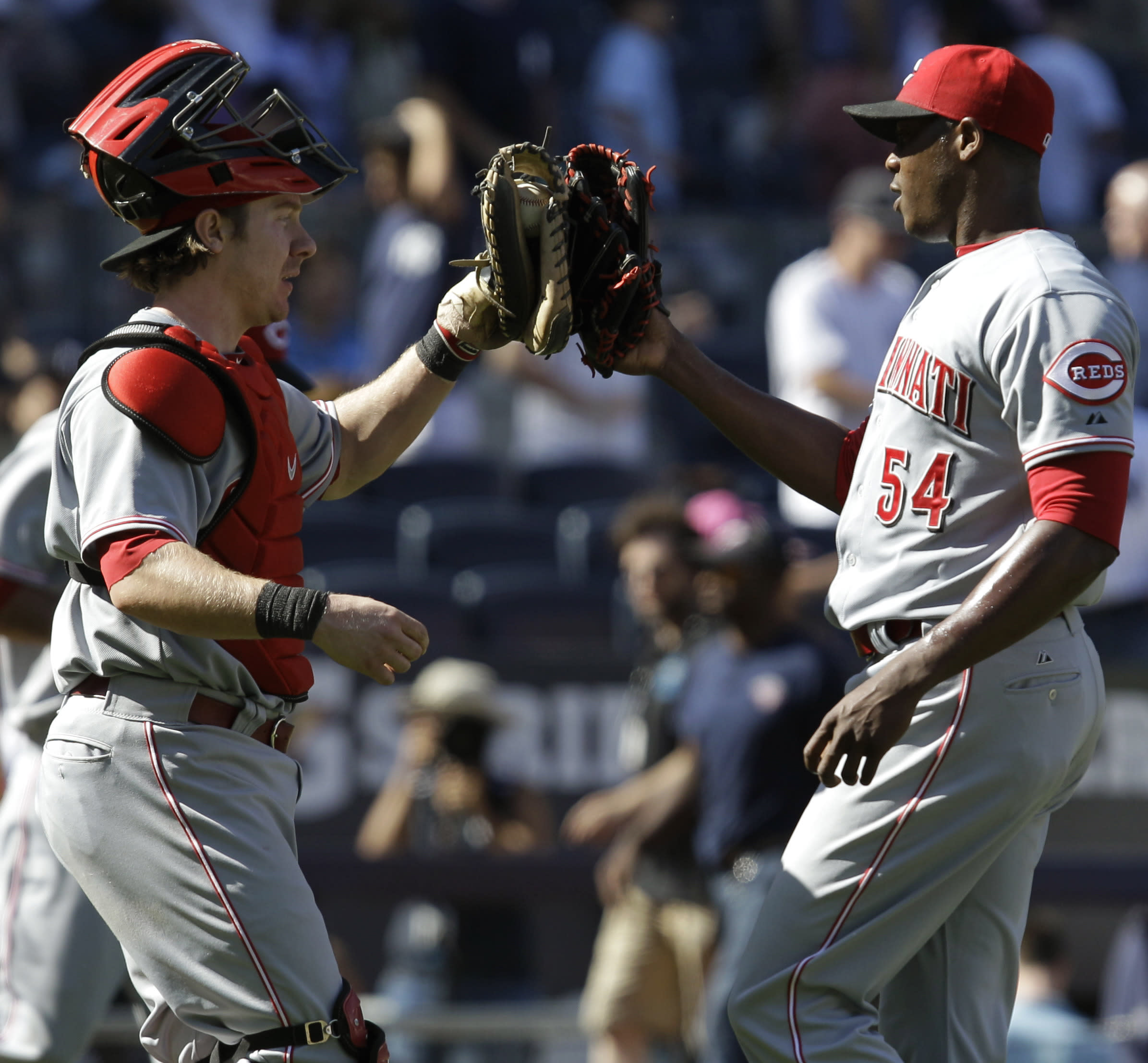 Cincinnati Reds catcher Ryan Hanigan, left, congratulates Reds reliever Aroldis Chapman, who closed out the Reds' 5-2 victory over the New York Yankees, after an interleague baseball game at Yankee Stadium in New York, Sunday, May 20, 2012. (AP Photo/Kathy Willens)