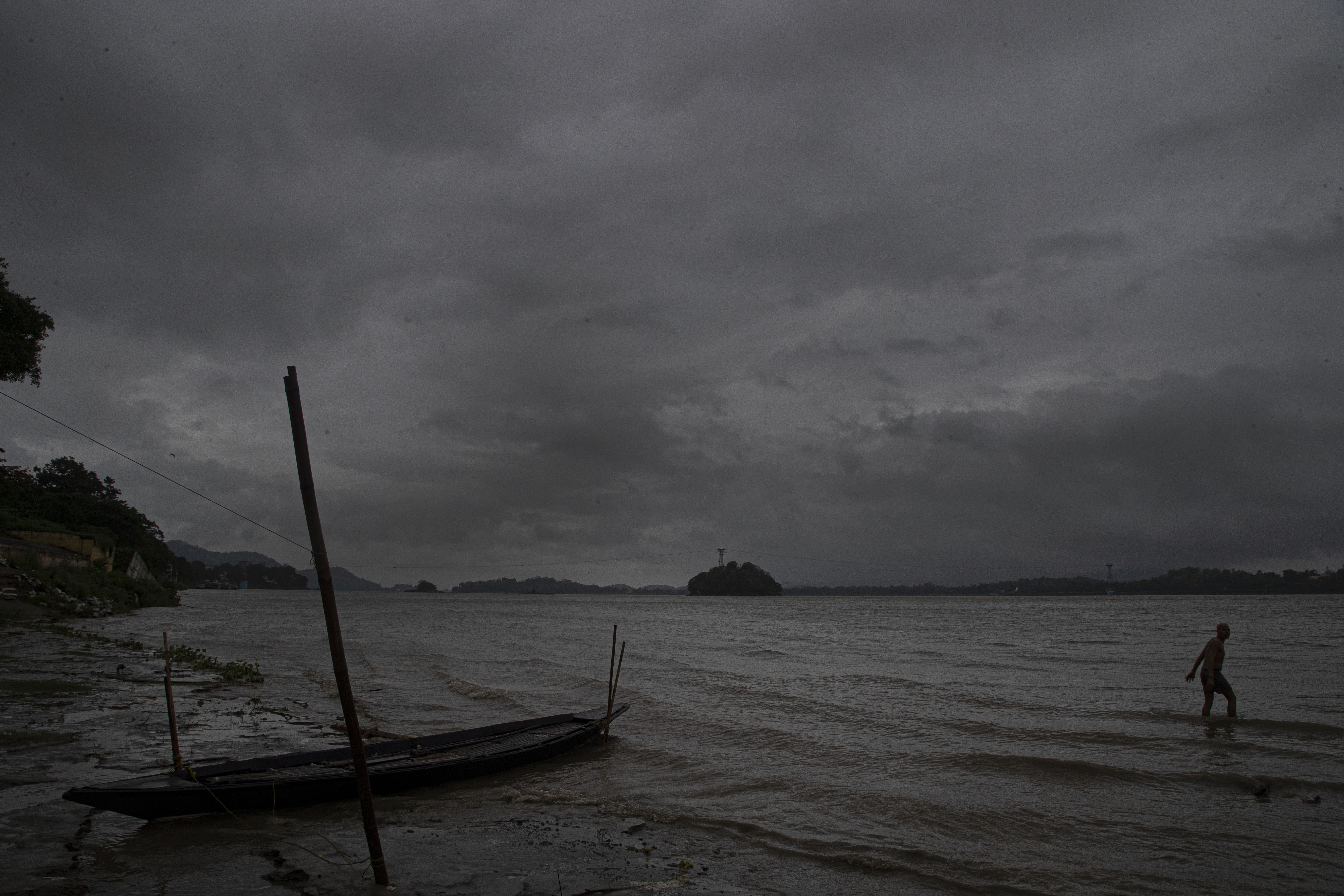 An Indian fisherman walks in the middle of heavy wind and rain in the river Brahmaputra in Gauhati, India, Thursday, May 21, 2020. A powerful cyclone ripped through densely populated coastal India and Bangladesh, blowing off roofs and whipping up waves that swallowed embankments and bridges and left entire villages without access to fresh water, electricity and communications. (AP Photo/Anupam Nath)