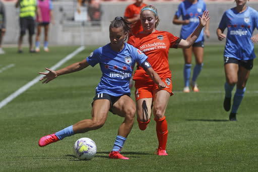 Chicago Red Stars' Sarah Gorden, front, plays the ball as Houston Dash's Bri Visalli defends during the second half of an NWSL Challenge Cup soccer finals match on July 26, 2020, in Sandy, Utah. Gordon aims to go beyond the social media statements, the T-shirts and the platitudes, and do something to lift up Black lives. The 28-year-old has put her focus on mental health for young women of color in launching her nonprofit organization, HoodSpace. (AP Photo/Rick Bowmer)