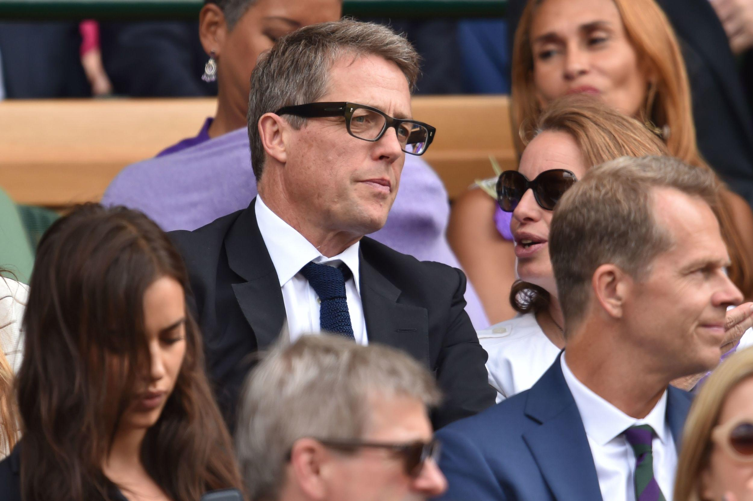 British actor Hugh Grant sits in the royal box on centre court.