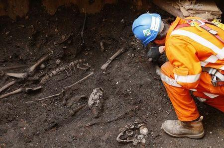 An archaeologist digs out skeletons from the site of the graveyard of the Bethlehem, or Bedlam, hospital next to Liverpool Street Station in the City of London, in this file photo taken on August 7, 2013. REUTERS/Andrew Winning