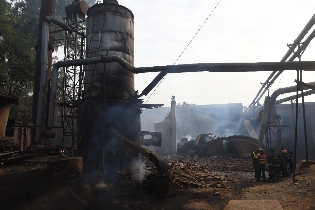 Pakistani rescue workers stand inside a burnt-out factory after it was torched by a mob in Jehlum on November 22, 2015 (AFP Photo/Farooq Naeem)