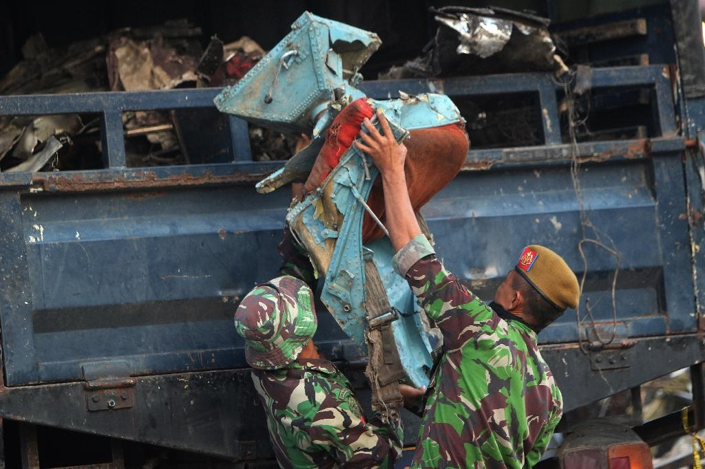 Soldiers load onto a truck an aircraft seat recovered from the Indonesian Air Force C-130 Hercules wreckage on July 1, 2015, a day after the plane crashed into a neighbourhood in Medan city (AFP Photo/Atar)