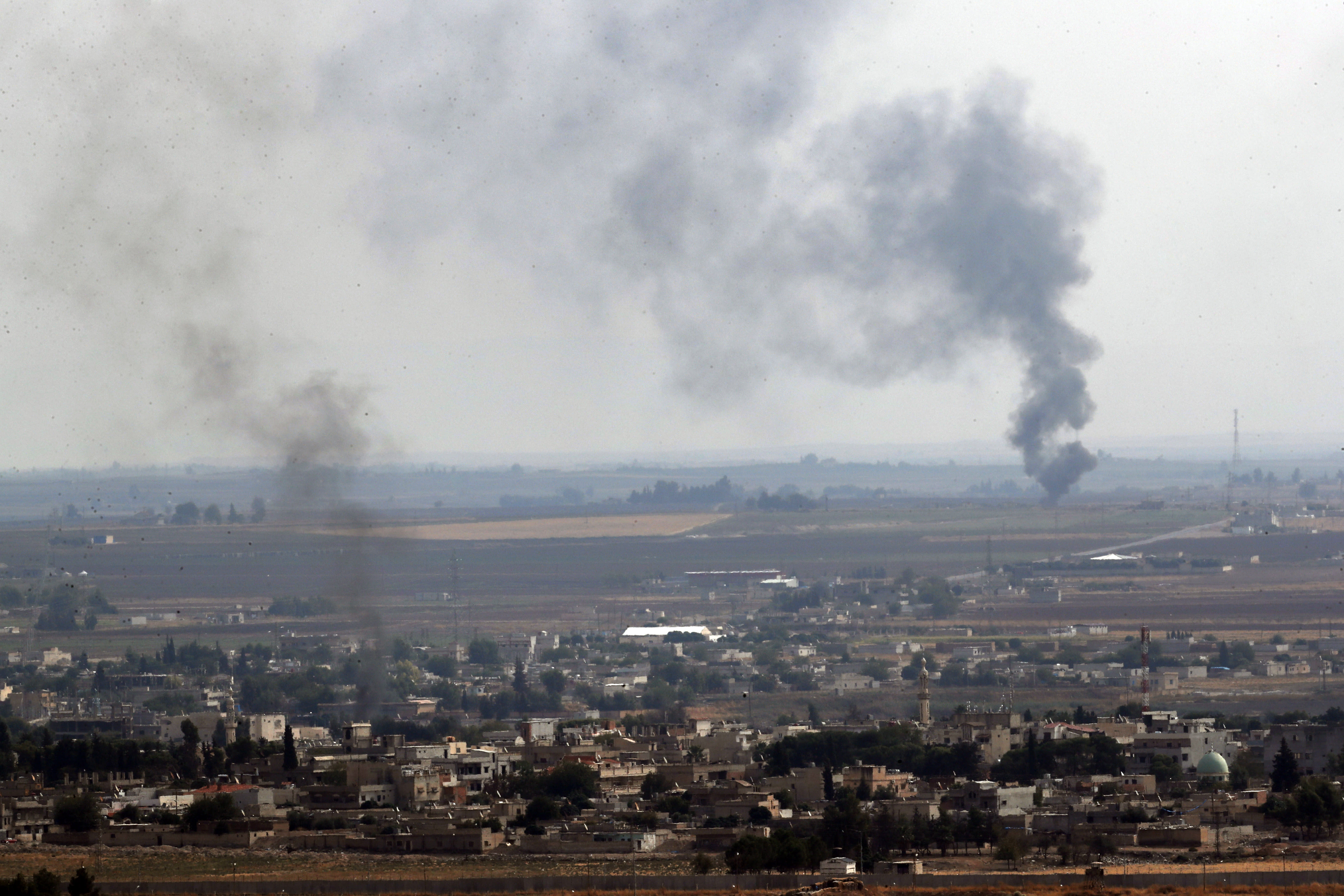 Turkish side of the border between Turkey and Syria in Ceylanpinar Sanliurfa province southeastern Turkey smoke billows from fires in Ras al-Ayn Syria Sunday Oct. 20 2019. Turkey's defense ministry says one soldie