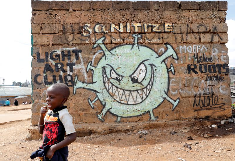 FILE PHOTO: A boy stands in front of a graffiti promoting the fight against the coronavirus disease (COVID-19) in the Mathare slums of Nairobi