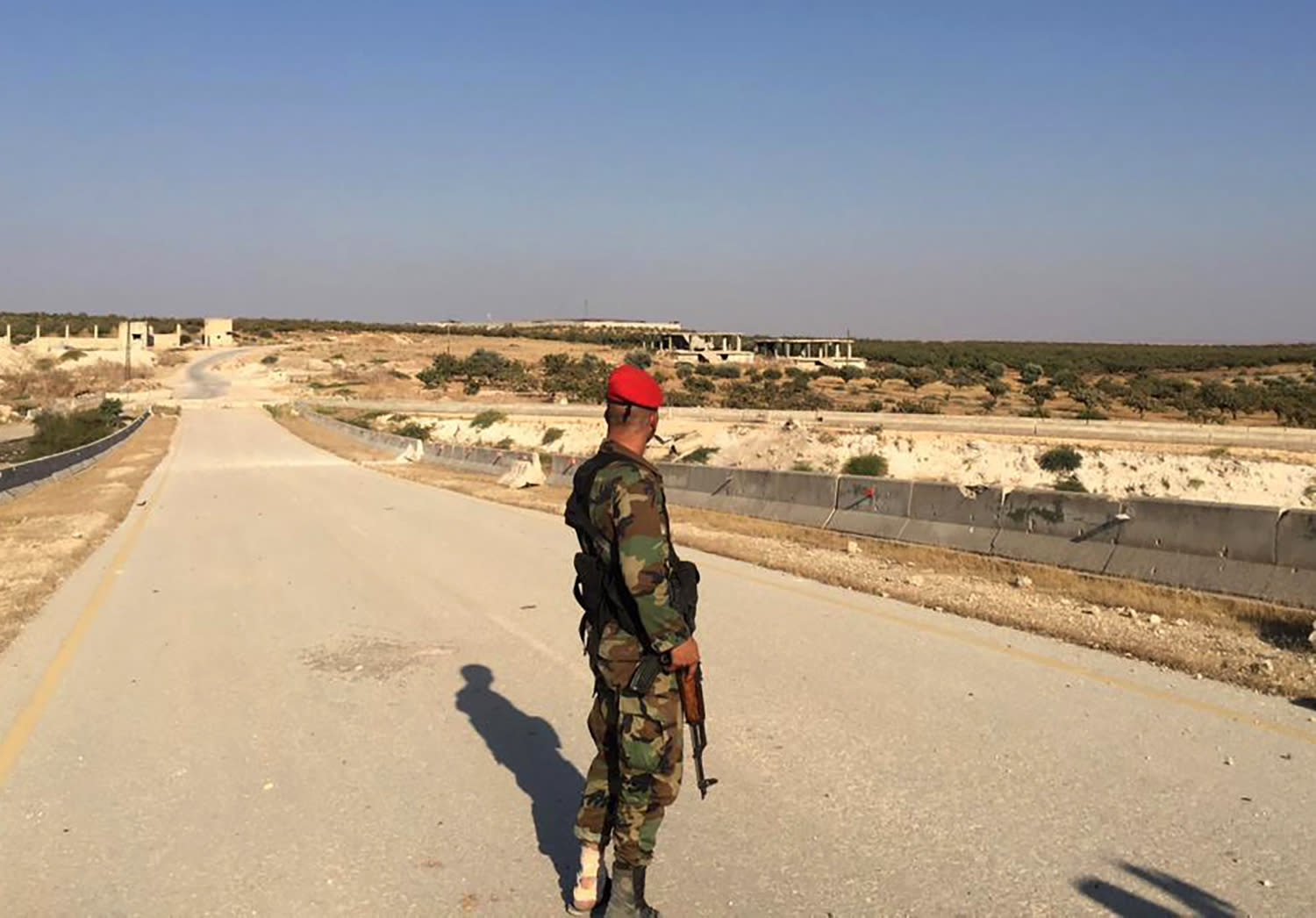 FILE - This Aug. 24, 2019, file photo, a Syrian soldier in the northwestern town of Khan Sheikoun, stands on the highway that links the capital Damascus with the northern city of Aleppo, Syria. The M5 highway, recaptured by President Bashar Assad's forces this week, is arguably the most coveted prize in Syria's civil war. The strategic highway is vital for Syria's economy as well as for moving troops. (AP Photo/Albert Aji, File)