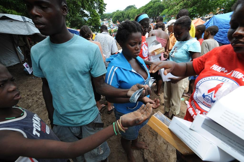 Members of a local NGO distribute condoms to people in Port-au-Prince, the capital of Haiti