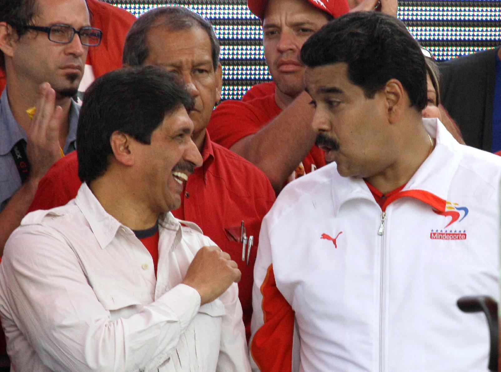 Venezuela's Vice President Nicolas Maduro, right, speaks with Argenis Chavez, a brother of President Hugo Chavez, during an event commemorating the 1958 fall of the country's dictatorship in Caracas, Venezuela, Wednesday, Jan. 23, 2013. Maduro said the government has uncovered a plot by unidentified groups to attack him and another senior leader. Maduro announced the purported plot while announcing that he would soon travel to Cuba along with Oil Minister Rafael Ramirez to see ailing President Hugo Chavez. (AP Photo/Fernando Llano)