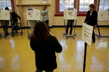 A voter casts his ballot behind a ballot booth during the U.S. presidential election at a polling station in the Bronx Borough of New York