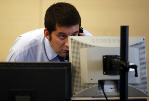 Broker checks his screens during a bond auction at a broker's office in Madrid