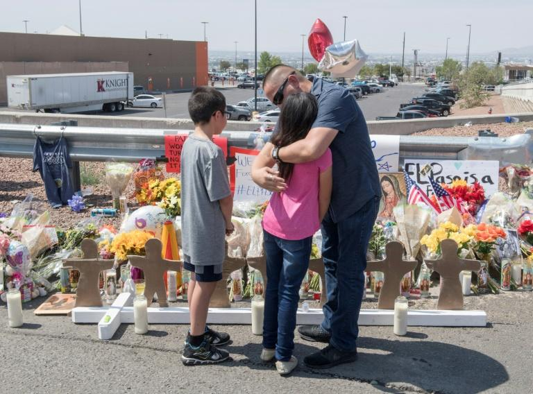 Members of the Soto family embrace beside a makeshift memorial after the shooting that left 22 people dead at the Cielo Vista Mall WalMart in El Paso, Texas, on August 5, 2019 (AFP Photo/Mark RALSTON)