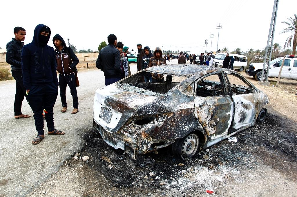 Security forces and locals gather at the site of an attack on a police checkpoint, near the town of Qadisiyah, 40km south of the holy Shiite Iraqi city of Najaf on January 1, 2017