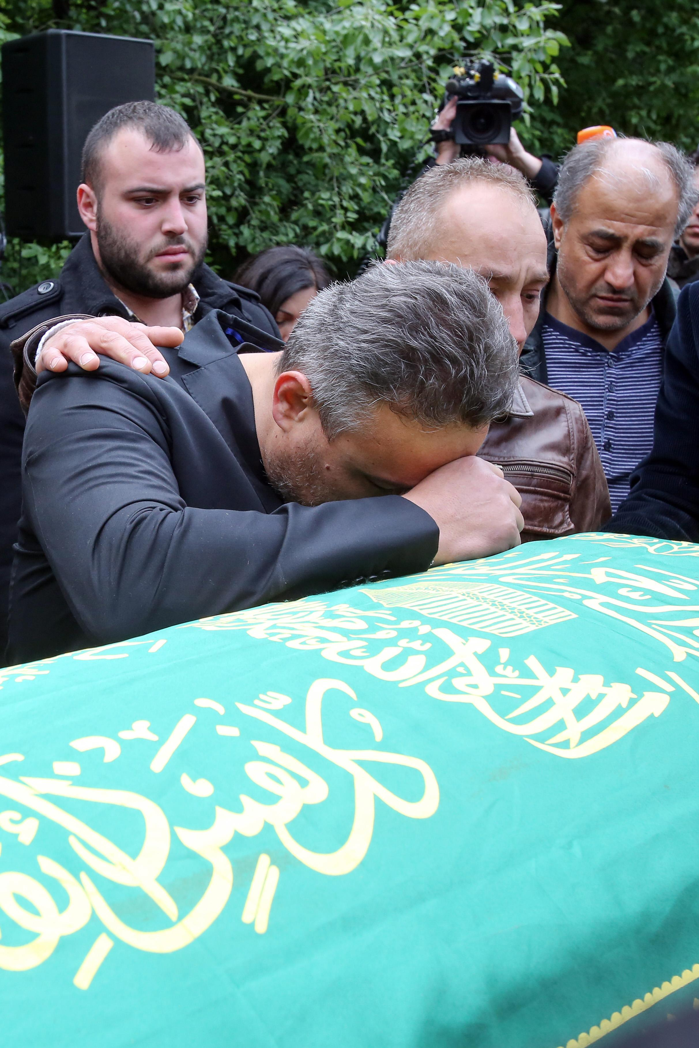 Celal Dede, front, mourns at the coffin of his son Diren during a funeral service in Hamburg, Germany, Sunday, May 4, 2014. More than 500 people were attending a memorial service for the 17-year-old German exchange student who was shot dead a week ago in the United States. (AP Photo/dpa, Bodo Marks)